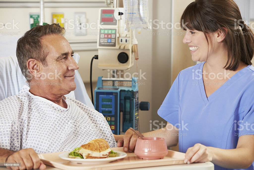 Patient Being Served Meal In Hospital Bed By Nurse stock photo