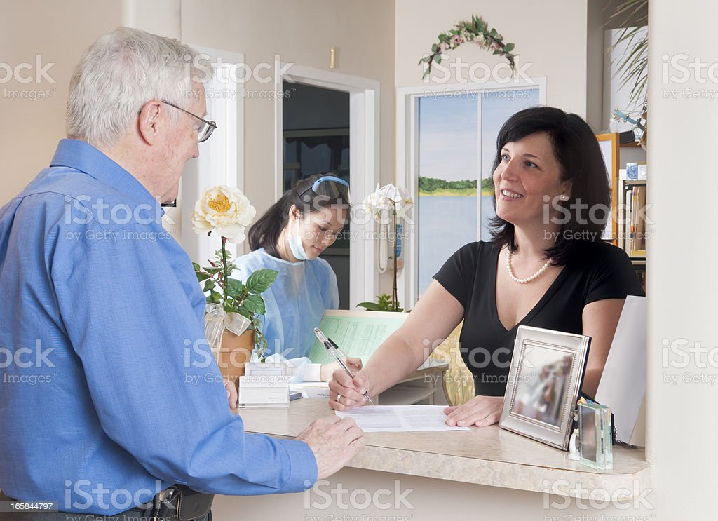 Patient Checking In At Reception For A Medical Appointment royalty-free stock photo