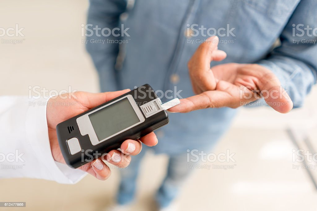 Patient checking sugar level with glucometer stock photo