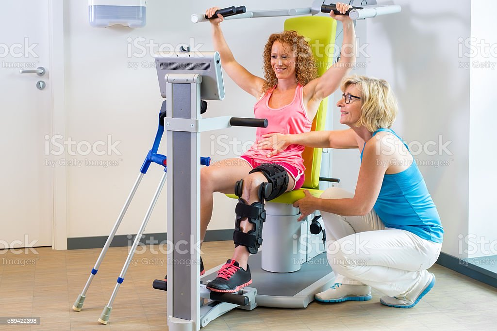 Patient getting help with leg rehabilitation. stock photo