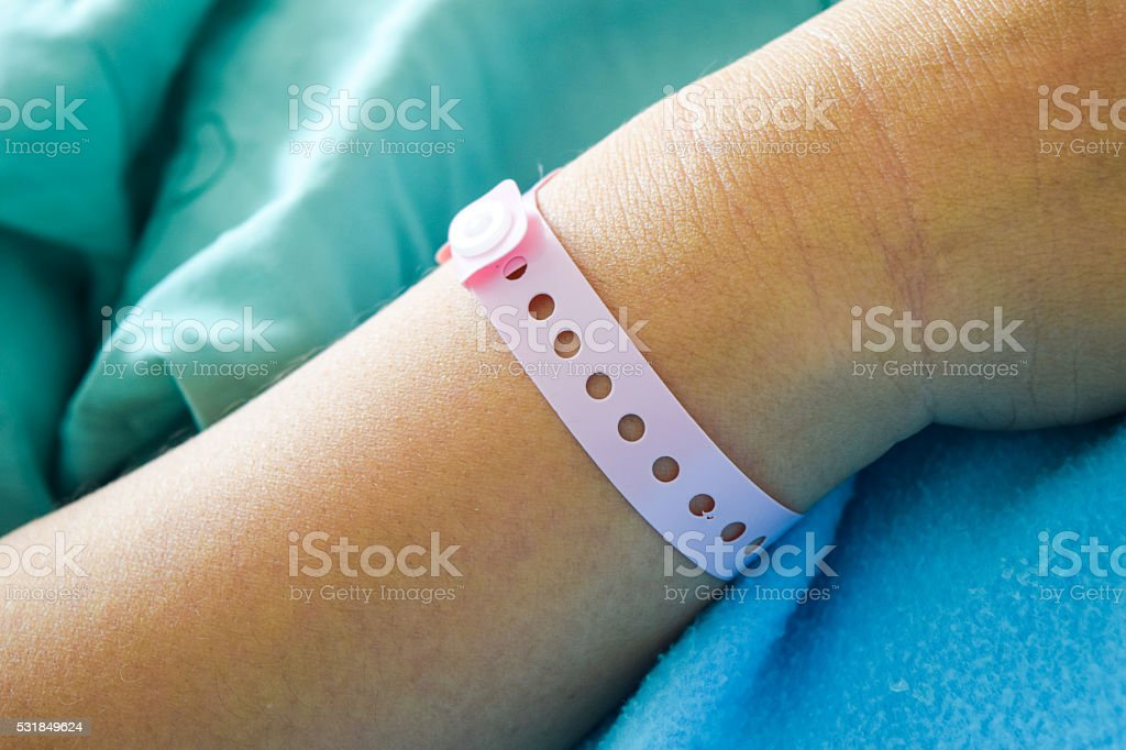 patient hand with hospital wrist tag stock photo