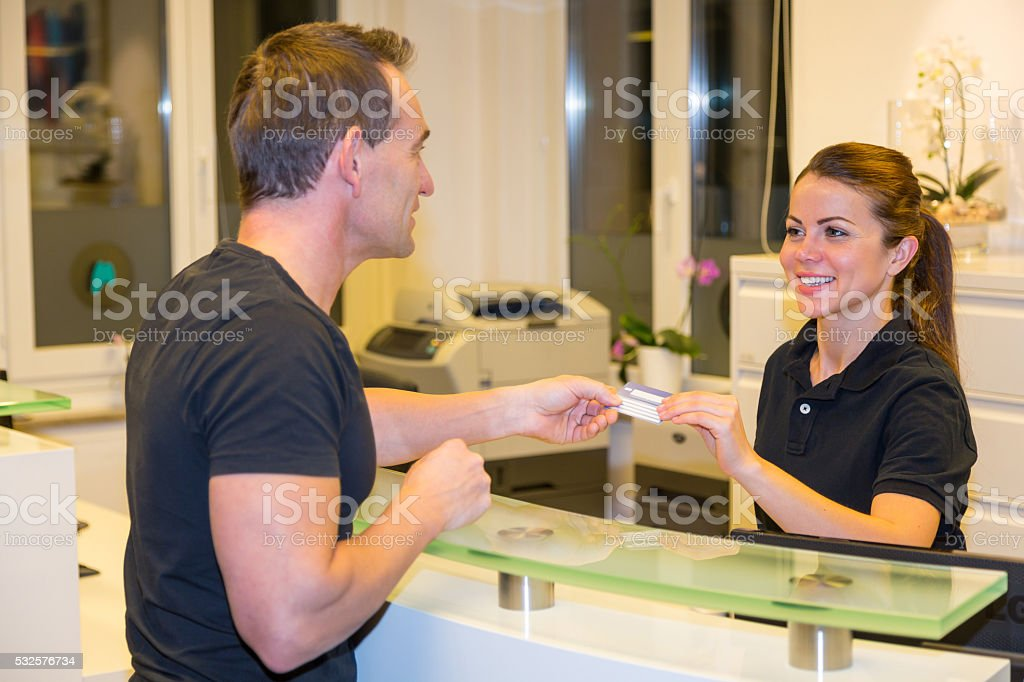Patient handing insurance card to doctor's receptionist stock photo