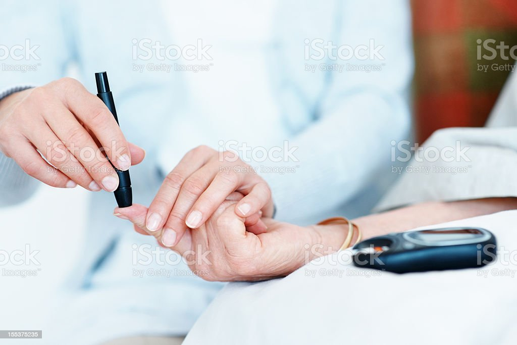 Checking her blood-sugar levels stock photo