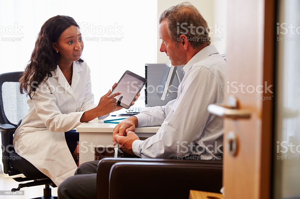 Patient Having Consultation With Female Doctor In Office stock photo