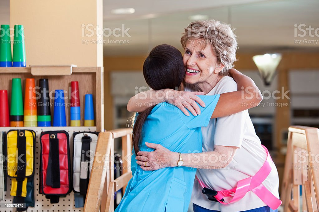 Patient hugging physical therapist stock photo