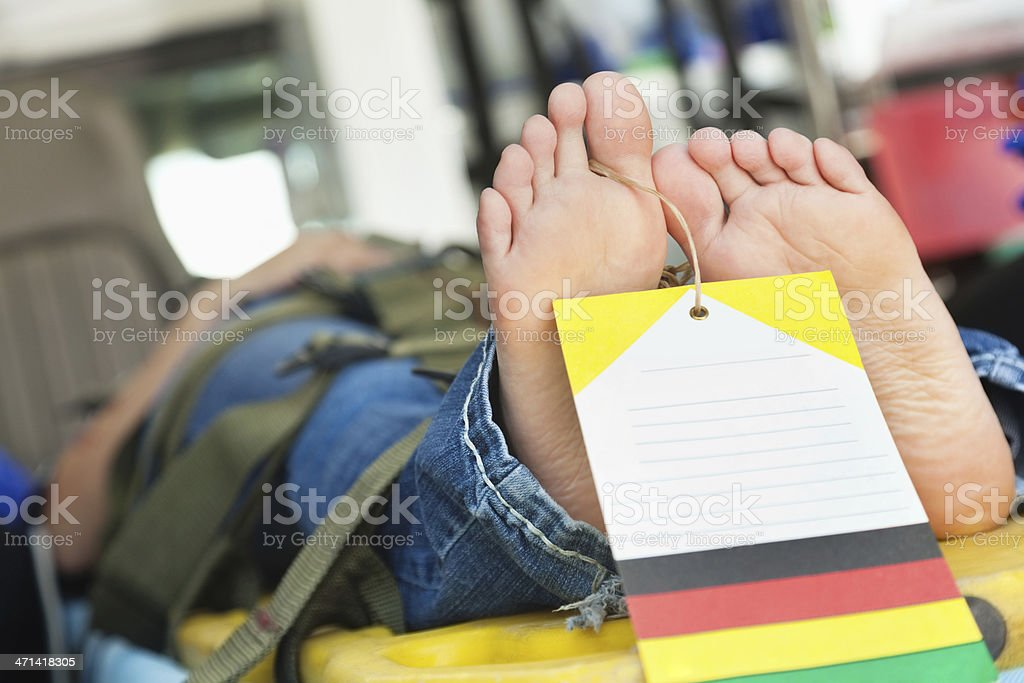 Patient in ambulance with death tag on her toe stock photo