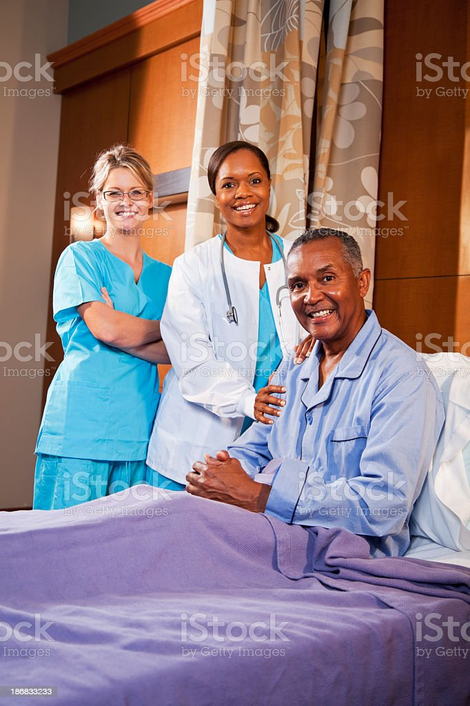 Patient in hospital bed with doctor and nurse stock photo