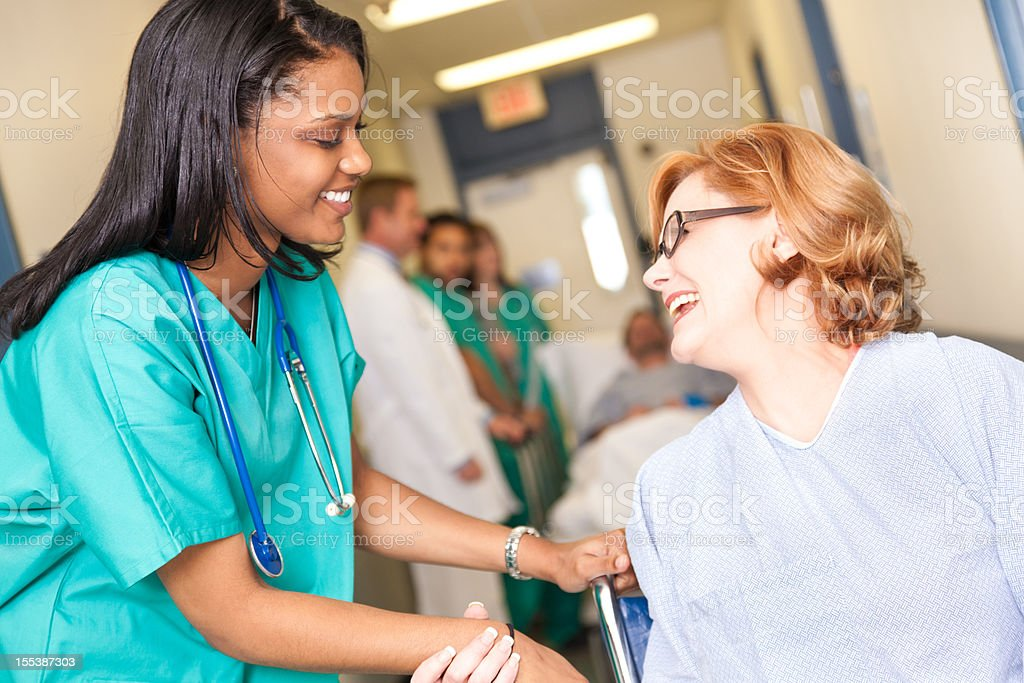 Patient in wheelchair at hospital being helped by caring nurse royalty-free stock photo
