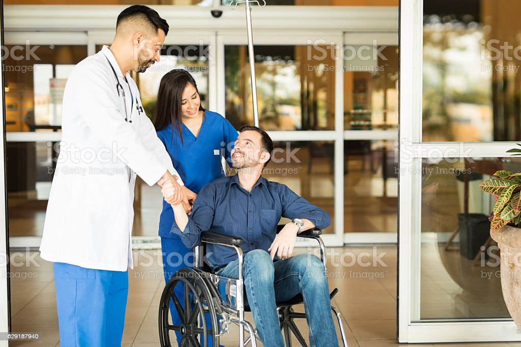 Patient leaving the hospital on a wheelchair stock photo