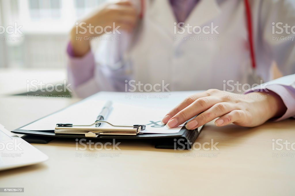 Patient listening intently to a male doctor explaining patient symptoms or asking a question as they discuss paperwork together in a consultation stock photo