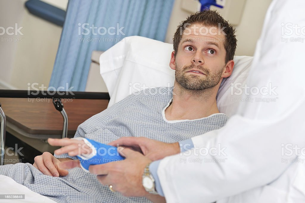 Patient listening to doctor about his hand in a caste royalty-free stock photo