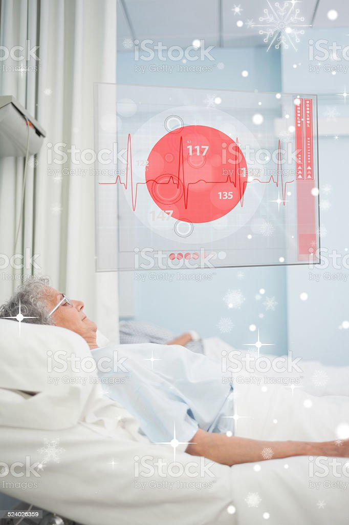 Patient lying in hospital bed with futuristic ecg data display stock photo