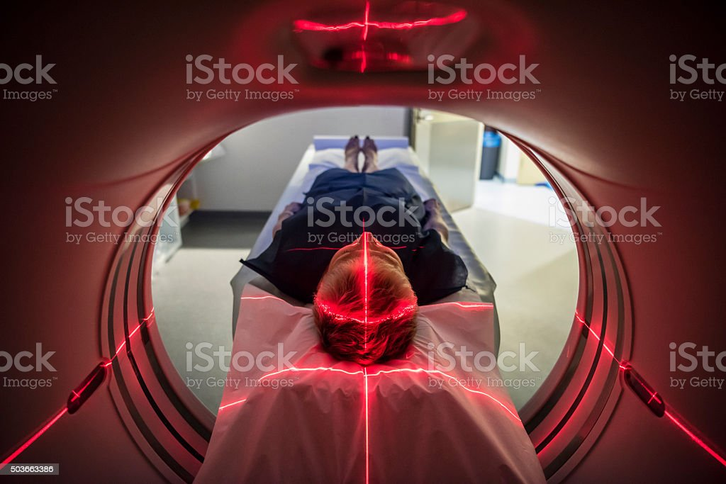 Patient lying inside a medical scanner in hospital stock photo