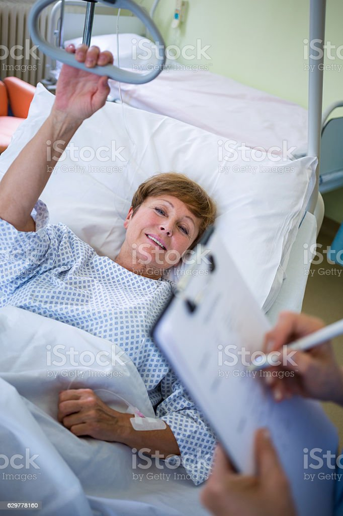 Patient lying on bed while nurse writing on clipboard stock photo