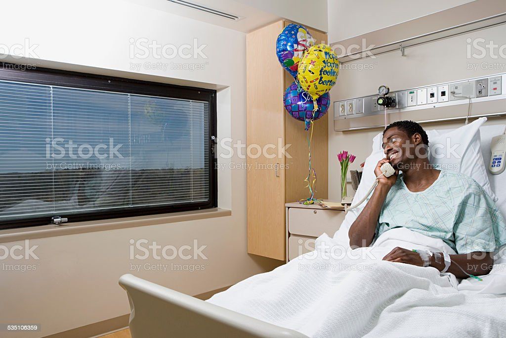 Patient on telephone in hospital bed stock photo