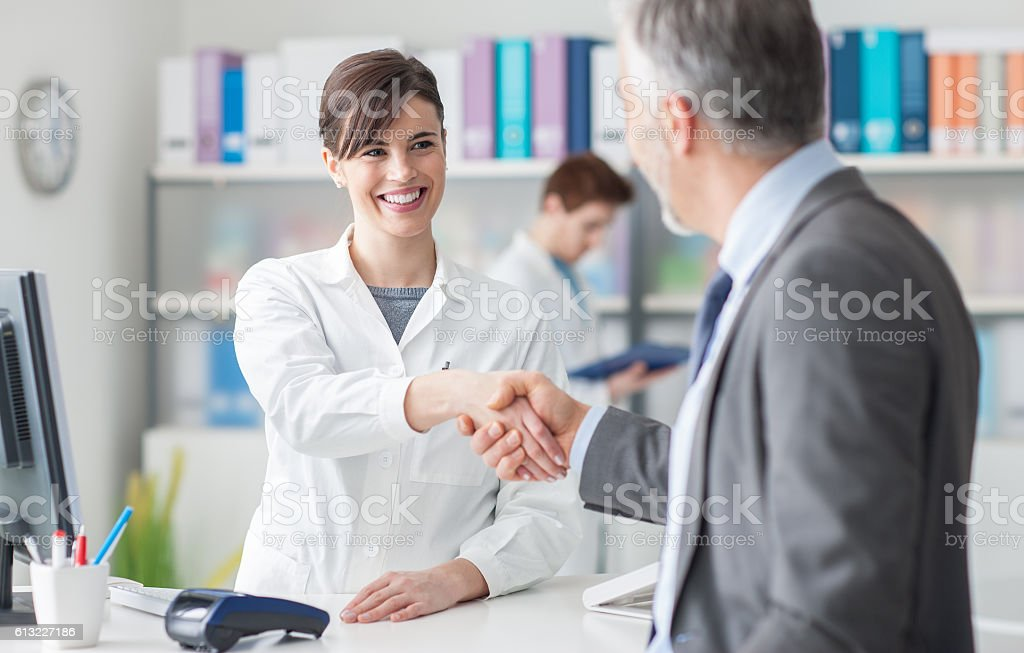 Patient shaking hands with a female doctor stock photo
