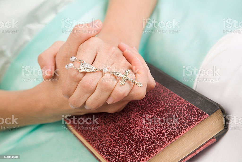 Patient silent prayer with rosary and bible stock photo