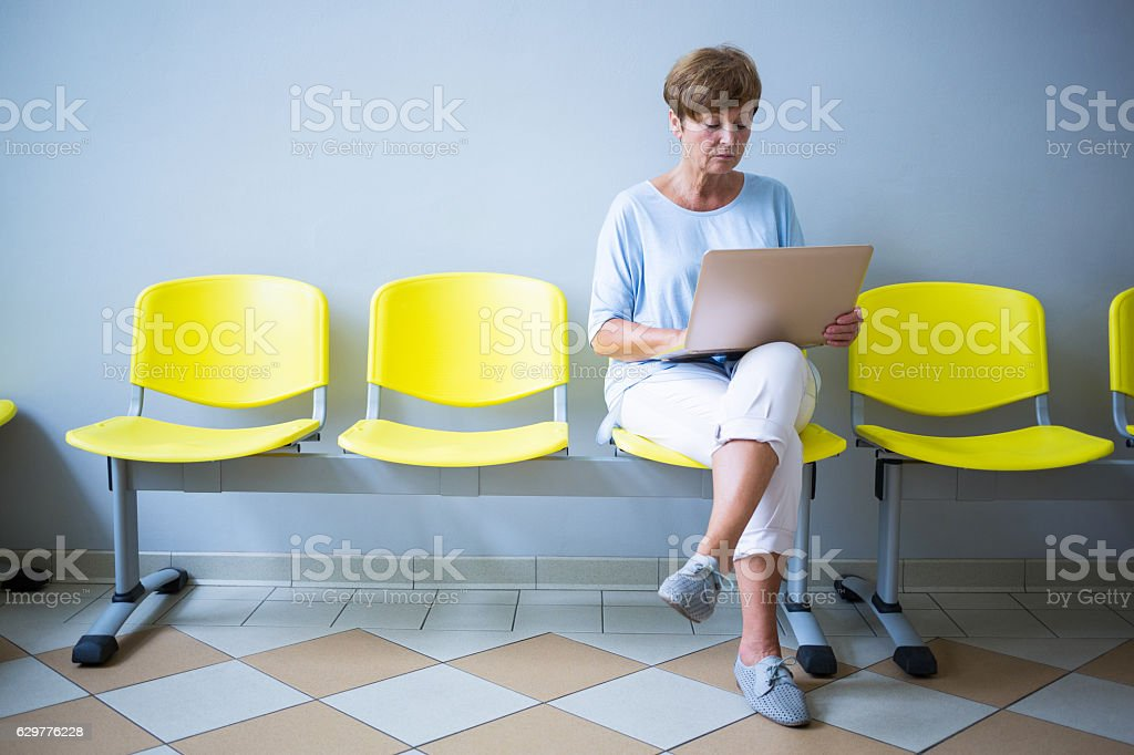 Patient sitting with report in a waiting room stock photo