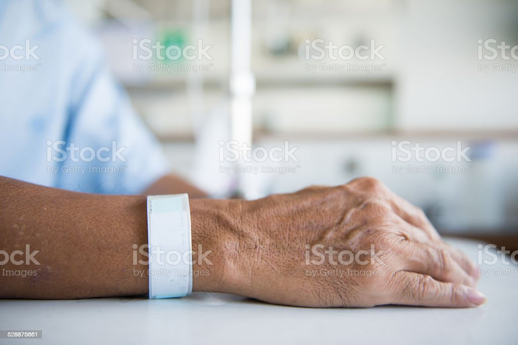 Patient with IV drip and hand tag stock photo