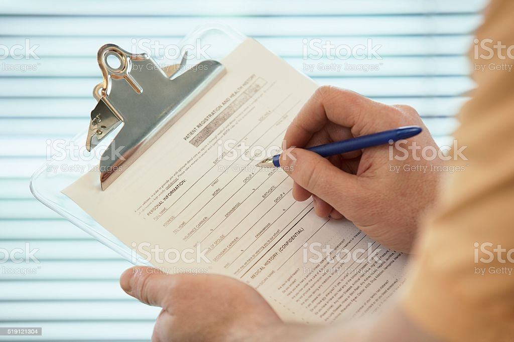 Patient writing on a clipboard stock photo