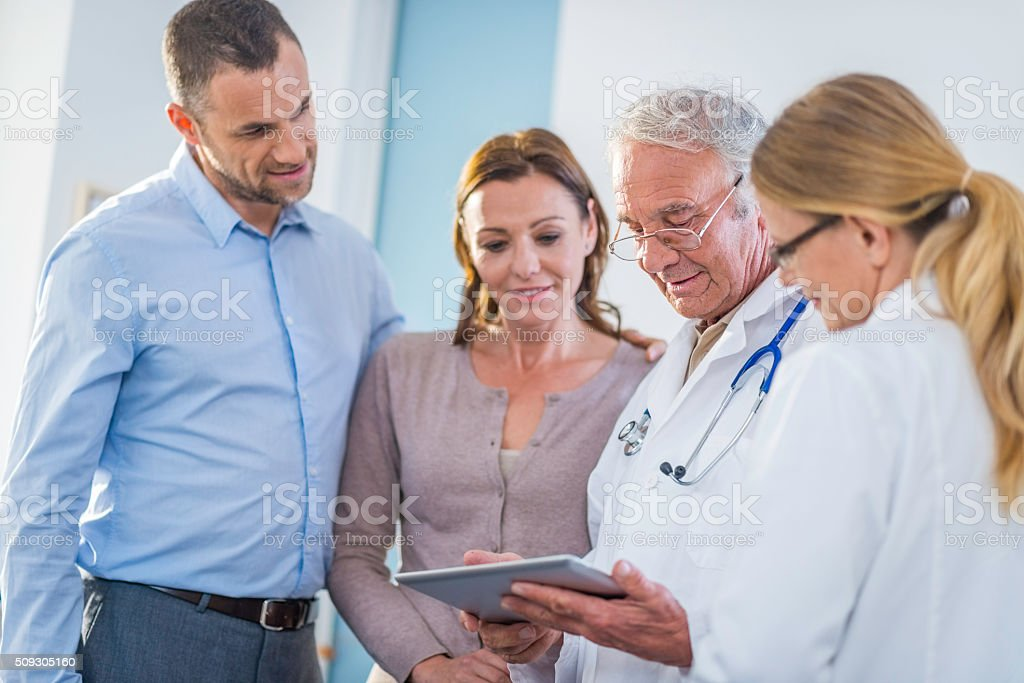 Patients and doctors examining test results on a digital tablet stock photo