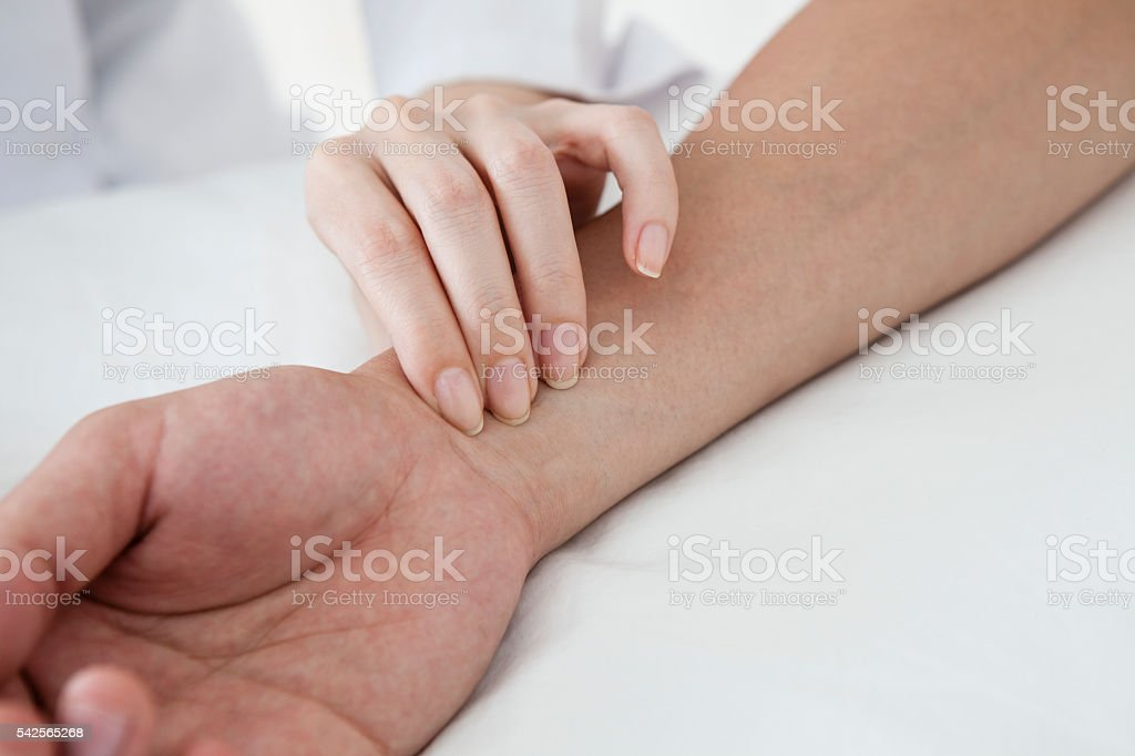 Patients in front of acupuncture have a test of  pulse stock photo
