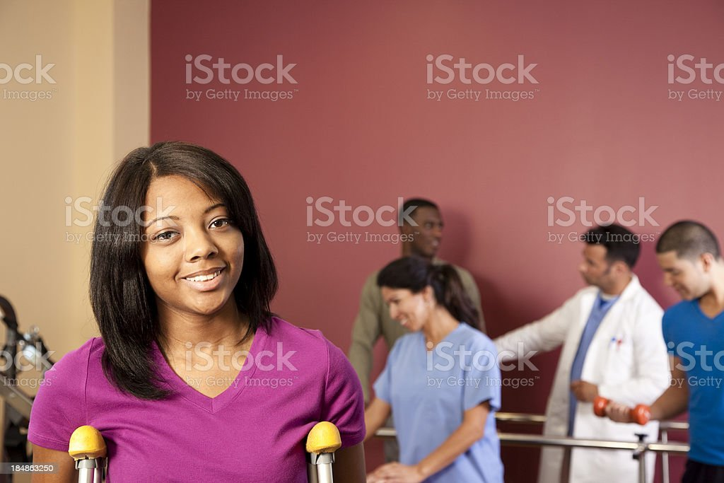 Patients in physical therapy office one on crutches  foreground. royalty-free stock photo
