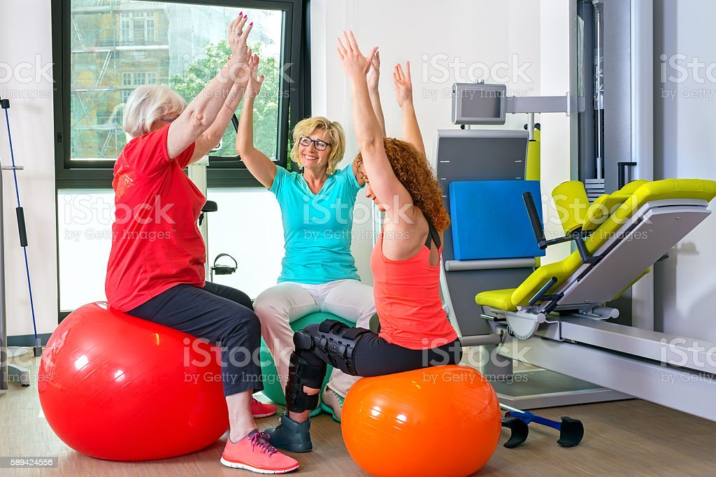 Patients on stability balls doing exercises. stock photo