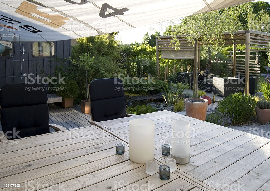 Patio and an outdoor dining area with a shade sail stock photo