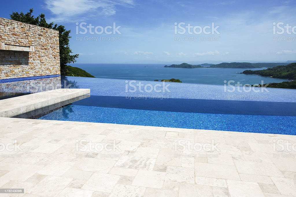 Patio and infinity pool over-looking the ocean stock photo