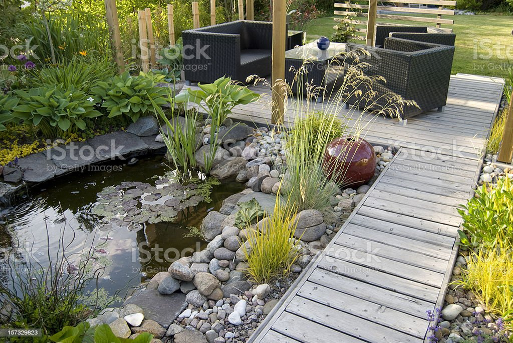 Patio and pond in the afternoon sun royalty-free stock photo