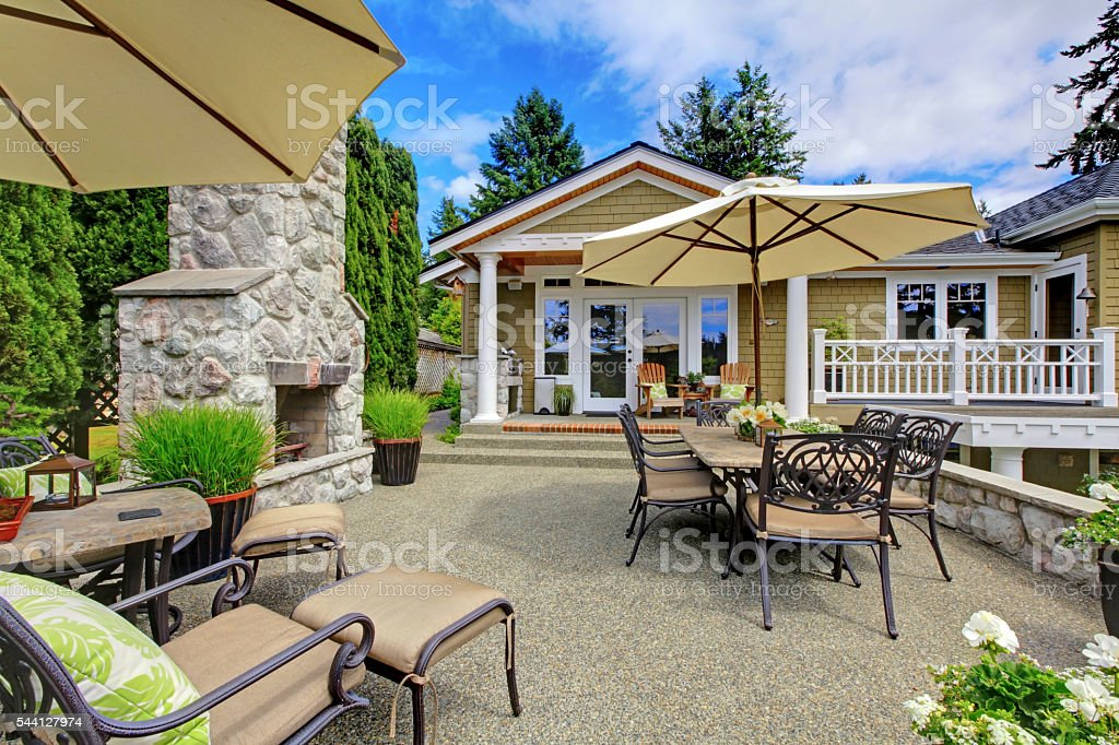 Patio area with stone fireplace and concrete floor. stock photo