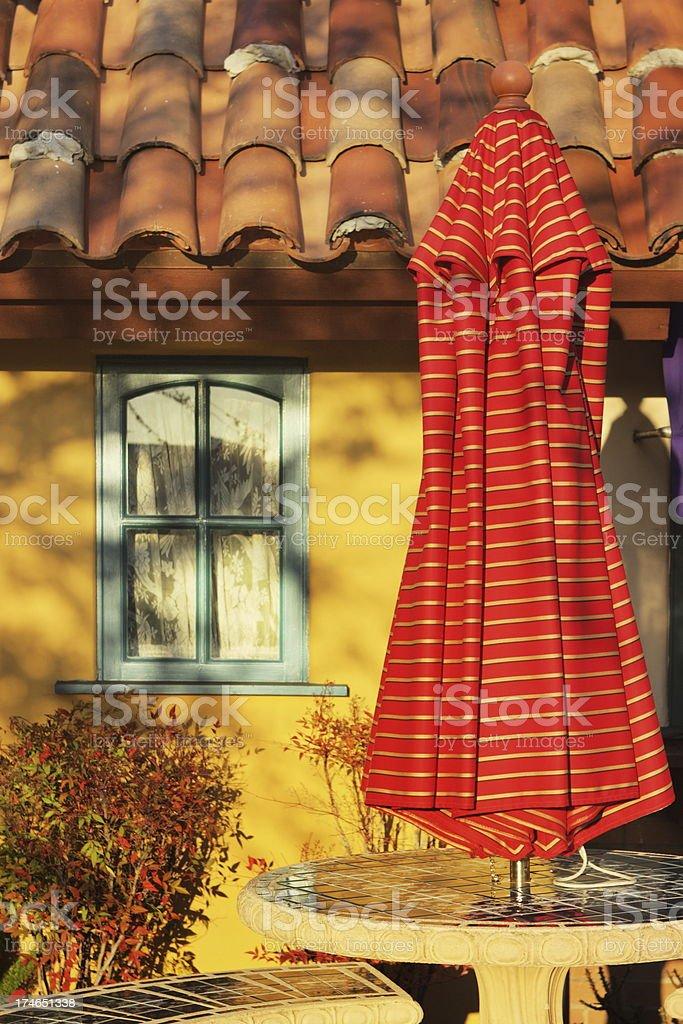 Patio decor umbrella in warm sunset light of quaint cottage exterior.