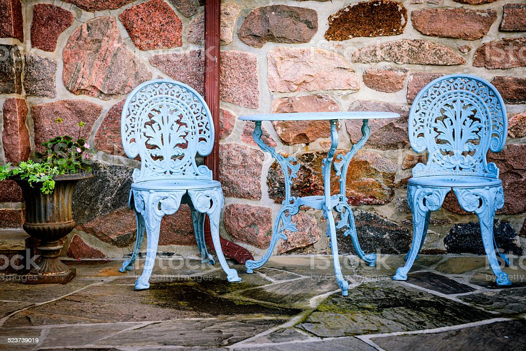 Patio furniture against stone wall stock photo
