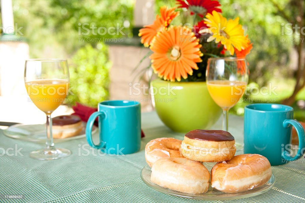 Patio table set with plate of fresh donuts and coffee royalty-free stock photo
