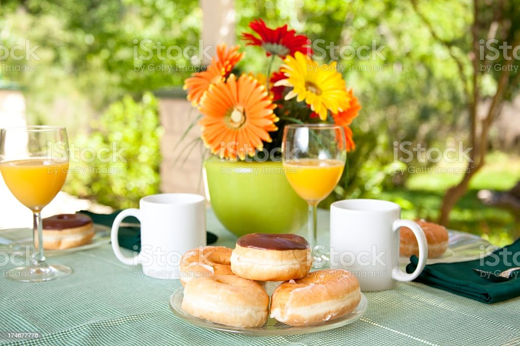 Patio table with plate of fresh donuts and orange juice royalty-free stock photo