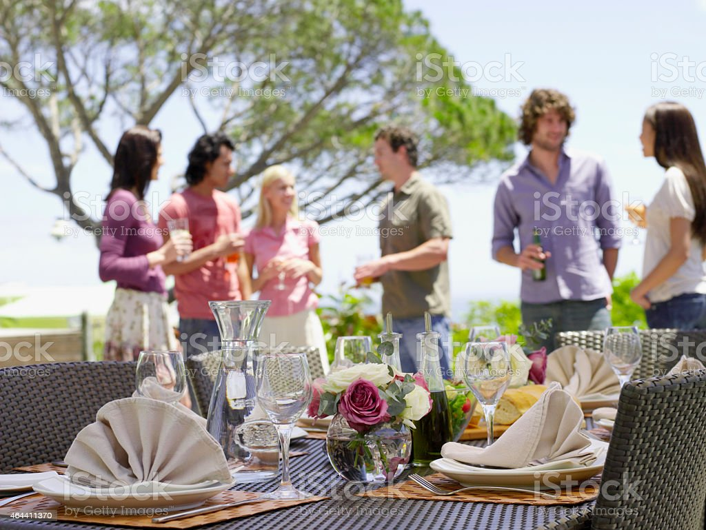 Patio table with wine glasses set up for lunch with friends stock photo