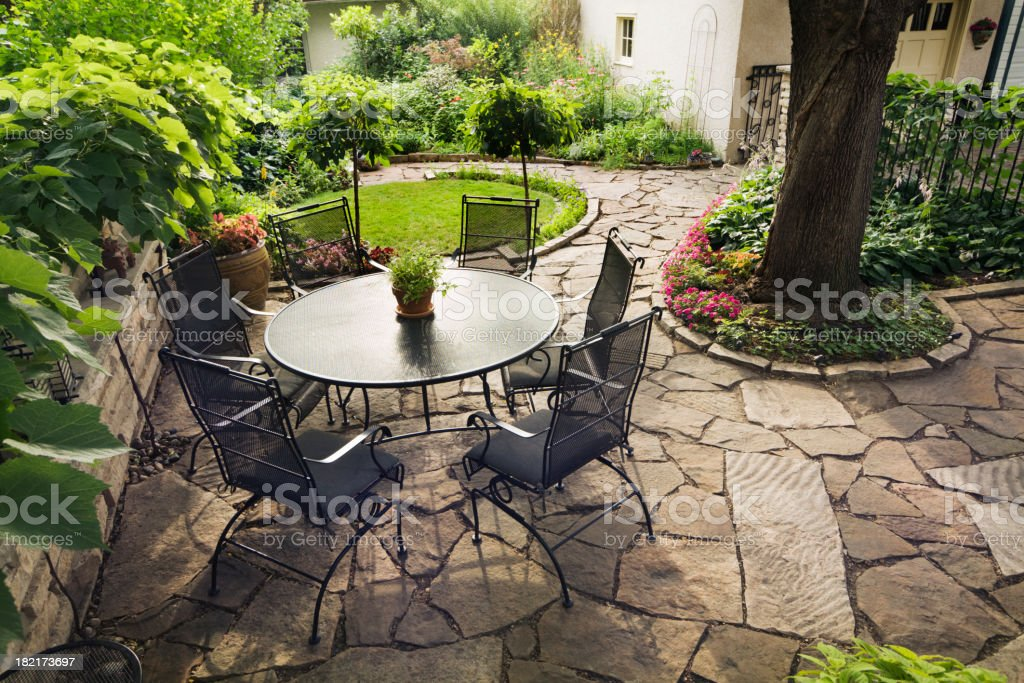Patio with Flower Garden and Furniture in Backyard Stone Landscaping royalty-free stock photo