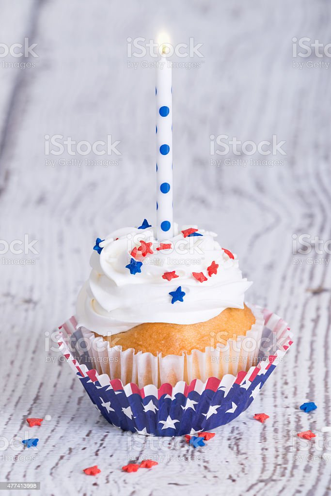 Patriotic 4th of July cupcake with a candle stock photo