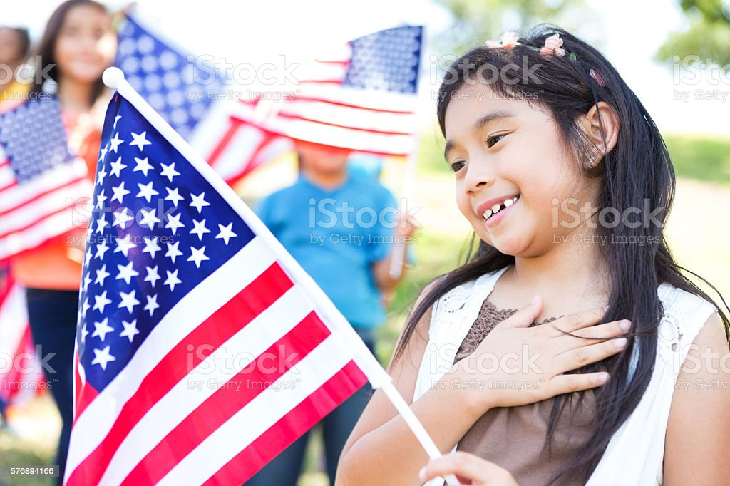 Patriotic Asian American girl with her hand over her heart stock photo
