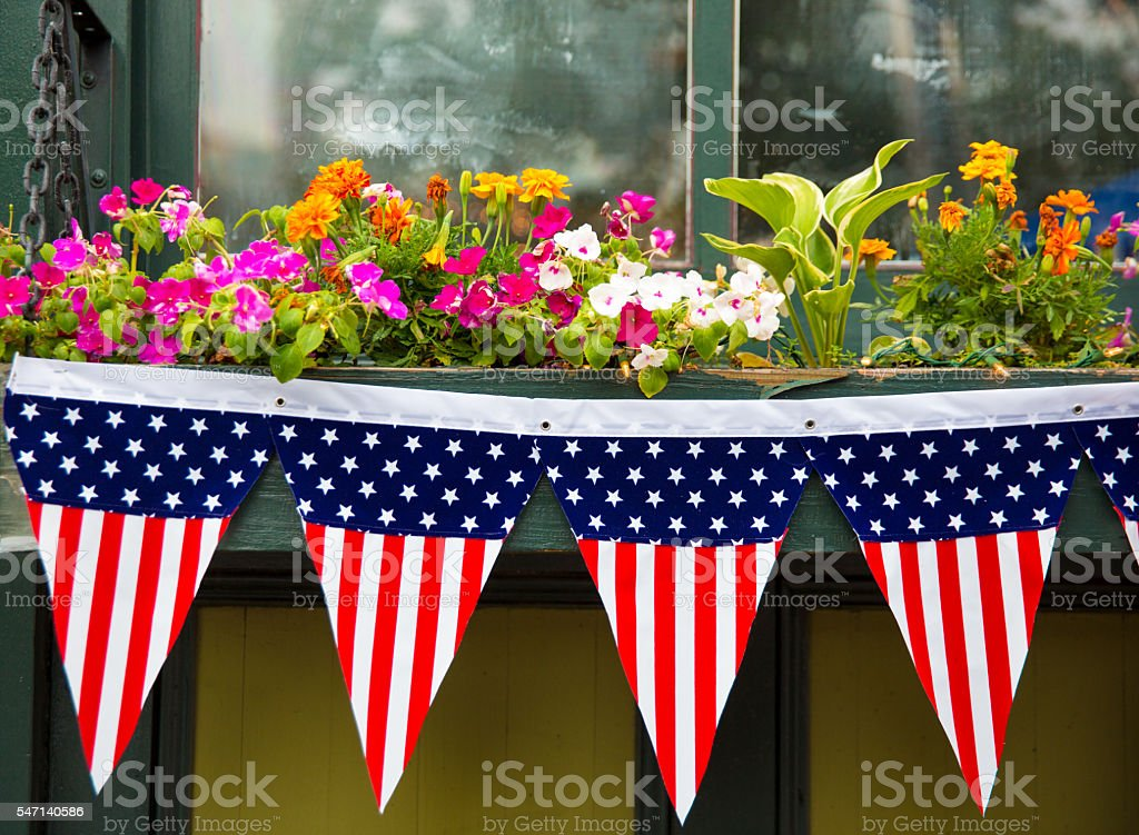 Patriotic display of flags on flower box for July 4th stock photo