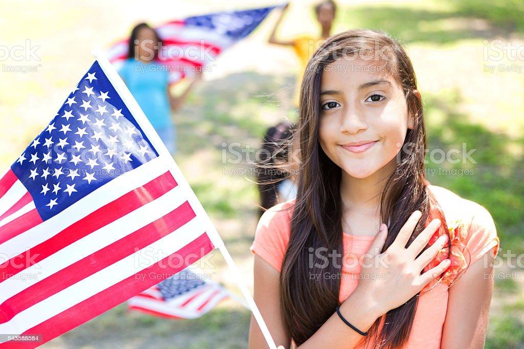 Patriotic preteen Hispanic little girl with American Flag stock photo