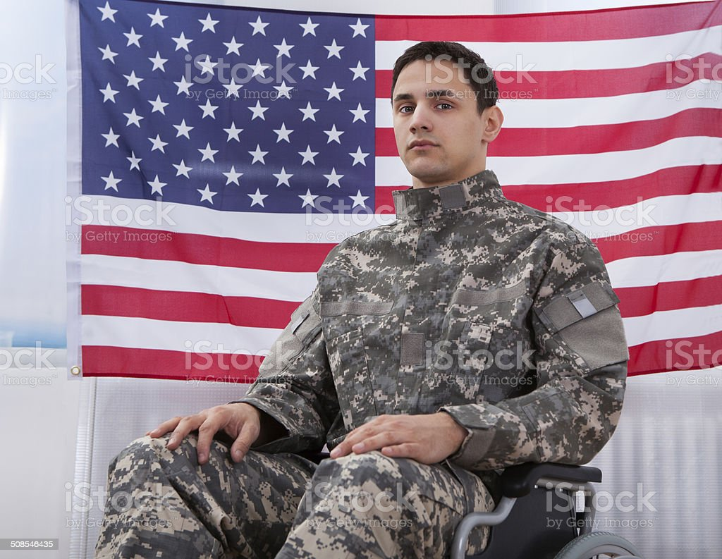 Patriotic Soldier Sitting On Wheel Chair Against American Flag stock photo