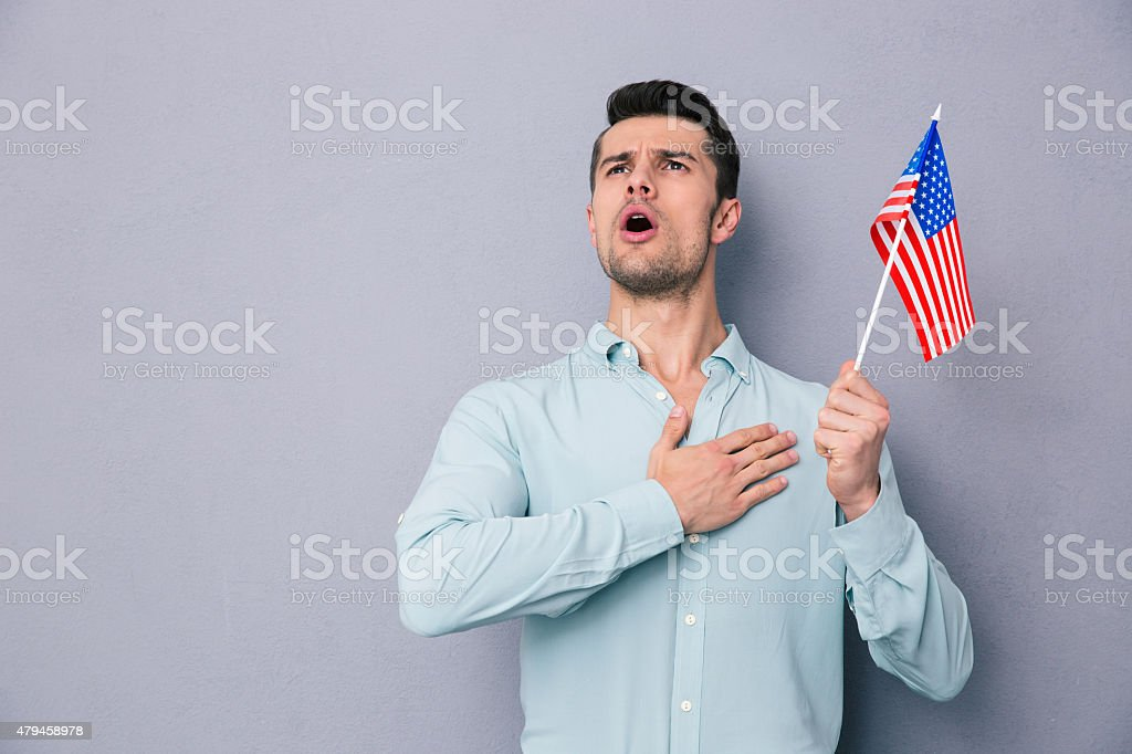 Patriotic young man holding US flag stock photo