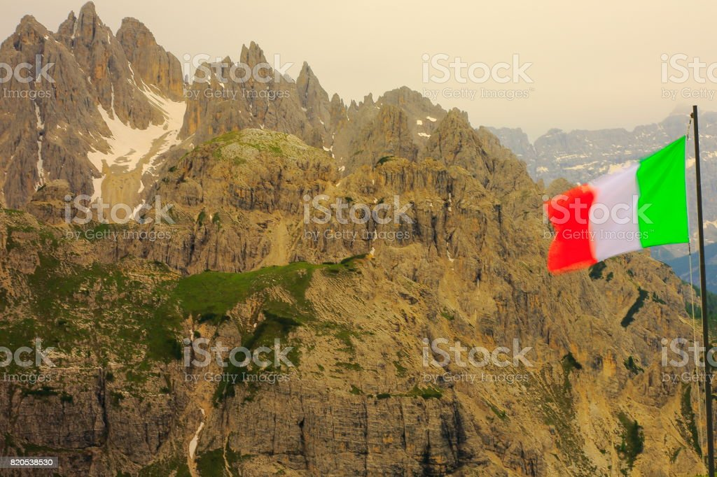 Patriotism: Italian flag winding above Idyllic Tre Cime di Lavaredo pinnacle and Auronzo di cadore massif mountain range and Puster valley, dramatic sky at moody sunrise dawn, dramatic panorama and majestic Dolomites, Italy tirol alps stock photo