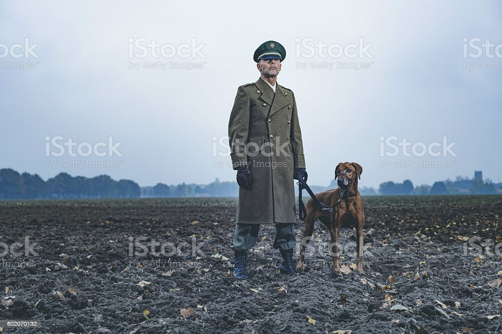 Patrolling retro 1940s military officer standing with dog on farmland. stock photo