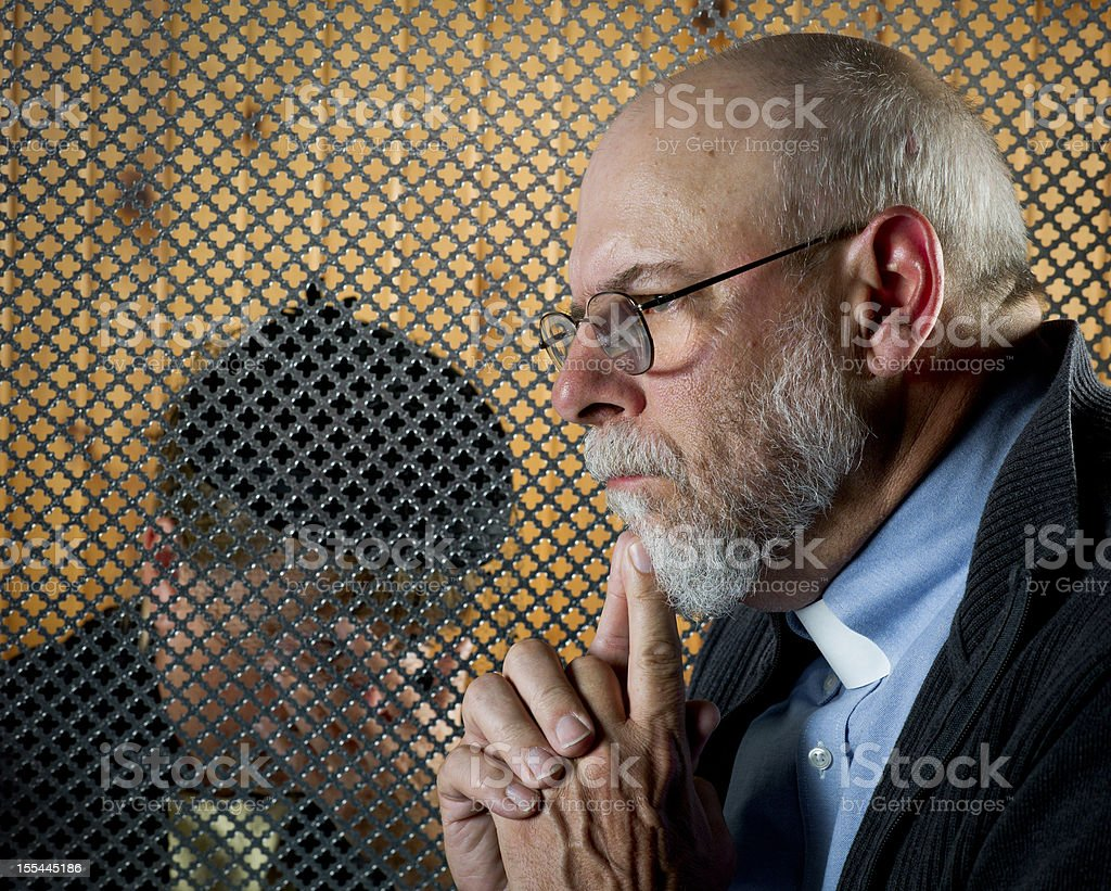 A patron giving a confession through a grate stock photo