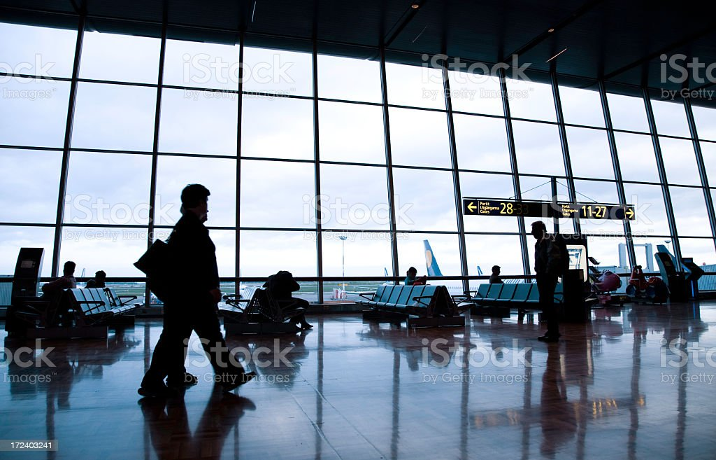 Patrons awaiting flights at an airport lobby royalty-free stock photo
