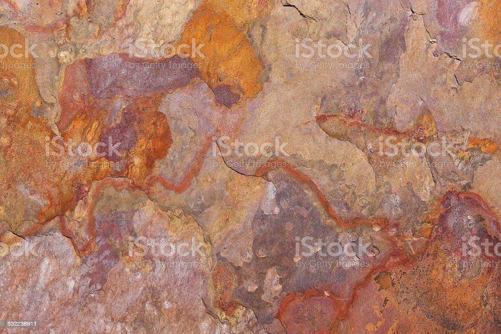 Pattern of a stone slab in rust, orange, beige, purple royalty-free stock photo