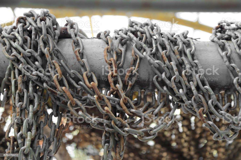 Pattern of thick rusty chain hang on iron rail. stock photo